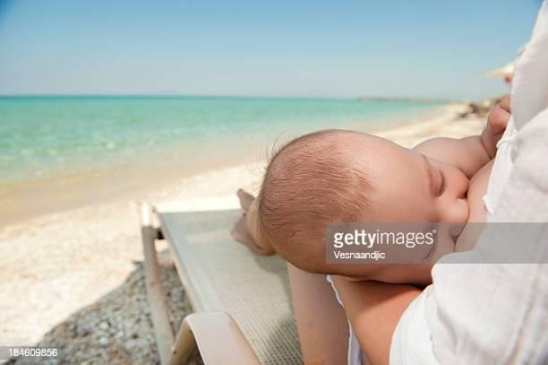 Baby breastfeeding on a sun lounger on the beach