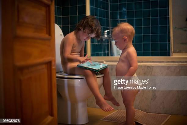 baby brothers in the bathroom - naakte kinderen stockfoto's en -beelden