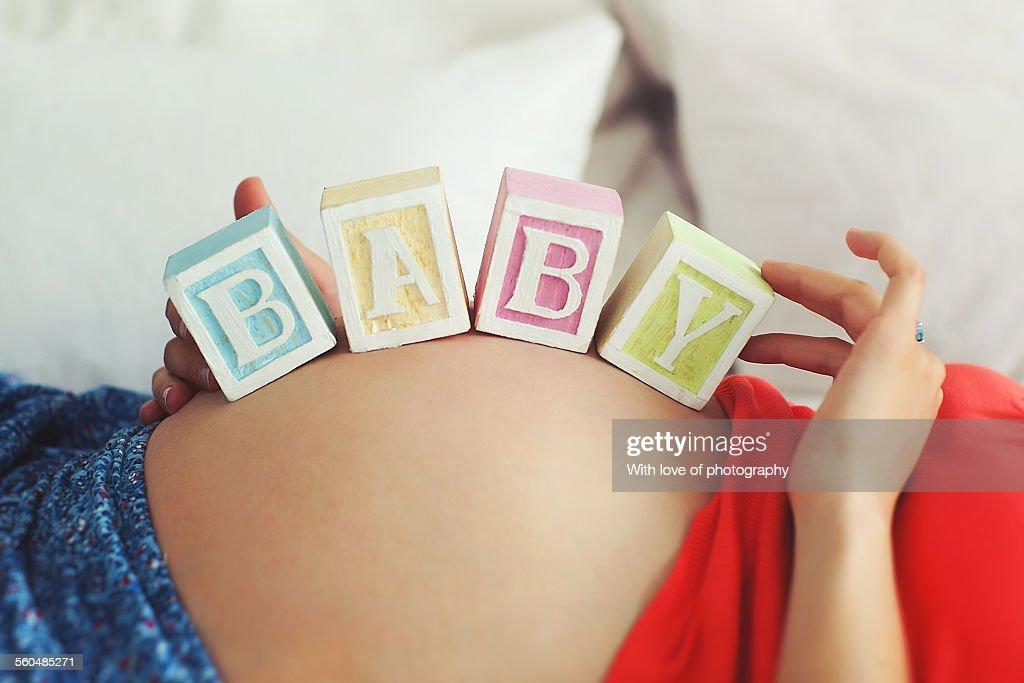 Baby bump with toy blocks BABY : Stock Photo