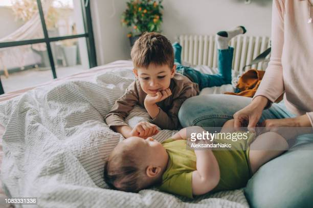 baby care - mum changing nappy stock pictures, royalty-free photos & images
