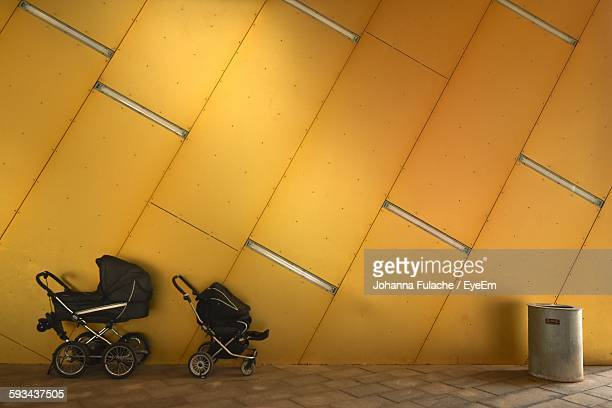 Baby Carriage Against Yellow Wall