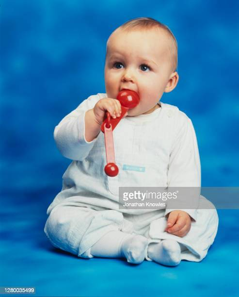 baby chewing on plastic measuring spoons - measuring spoon stock pictures, royalty-free photos & images