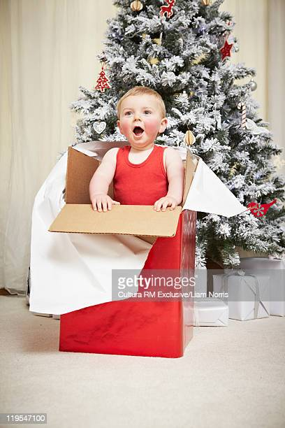Baby climbing out of wrapped present