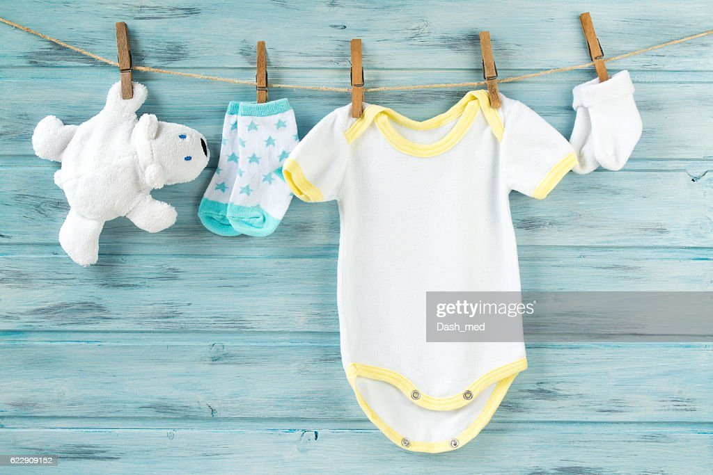 Baby clothes, onesie, socks, white bear toy on a clothesline : ストックフォト
