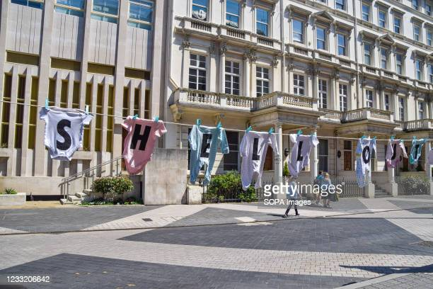 Baby clothes with letters spelling Shell Out hang outside the Science Museum in London during the Extinction Rebellion anti-Shell protest. The...