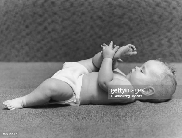 A baby contemplates the sole of its foot circa 1950