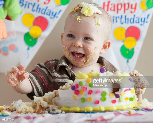 Baby covered in birthday cake