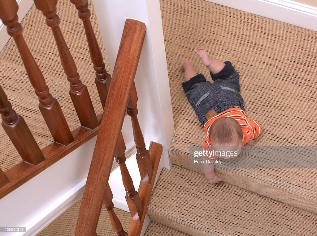Baby crawling about to fall downstairs : Stock Photo