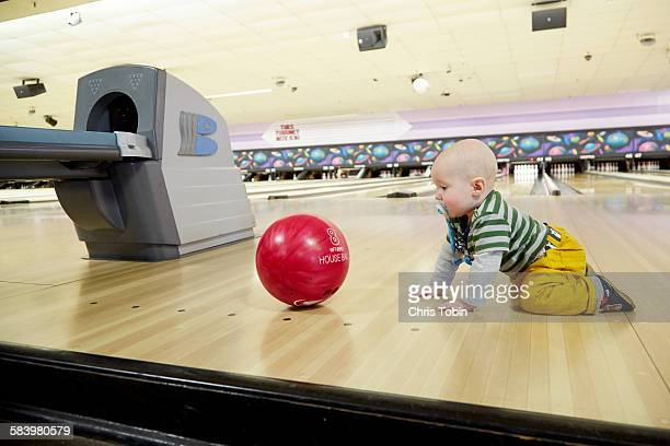 Baby crawling after bowling ball
