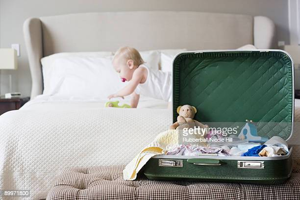 baby crawling bed next to an open suitcase