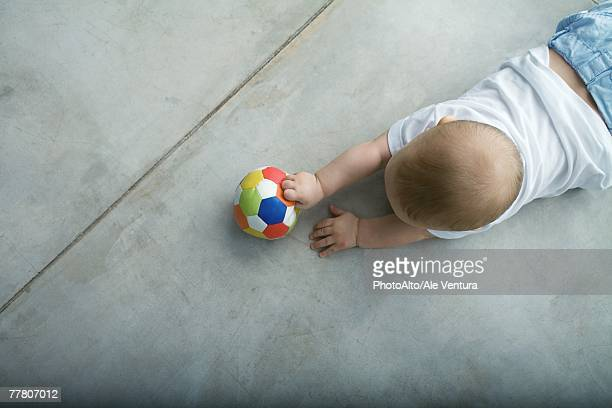Baby crawling on floor, holding ball, view from directly above