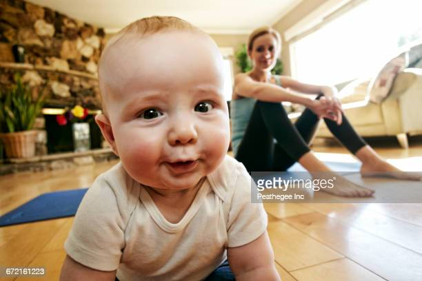 Baby crawling on floor while mother rests from workout