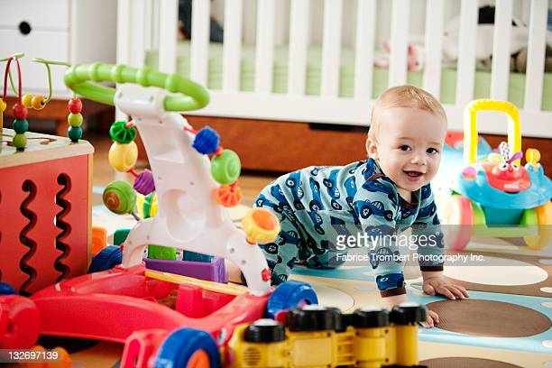 baby crawling with toys - baby toys stock photos and pictures