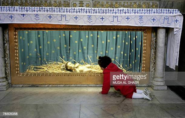 A baby crawls near a statue depicting baby Jesus at the Church of Nativity the alleged birth place of Jesus Christ in the West Bank town of Bethlehem...