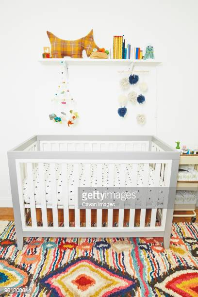 Baby crib and toys in bedroom at home