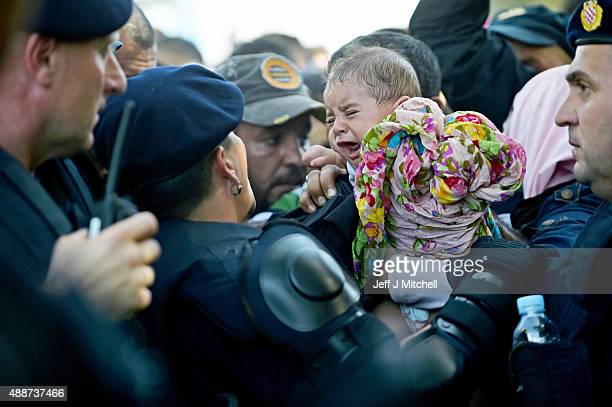 A baby cries as migrants force their way through police lines at Tovarnik station to board a train bound for Zagreb on September 17 2015 in Tovarnik...