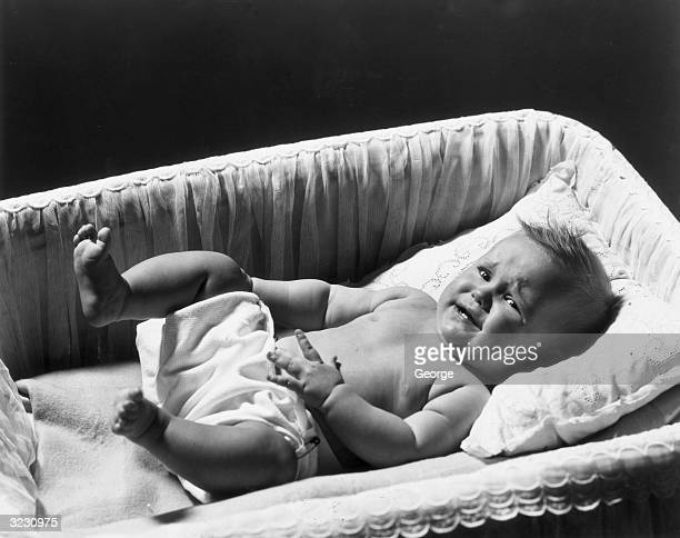 A baby cries while laying in a crib with her hands and feet in the air