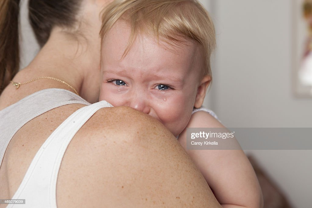 A baby crying and leaning on her mother's shoulder : Stock Photo