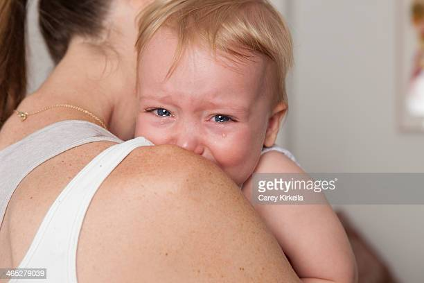 A baby crying and leaning on her mother's shoulder