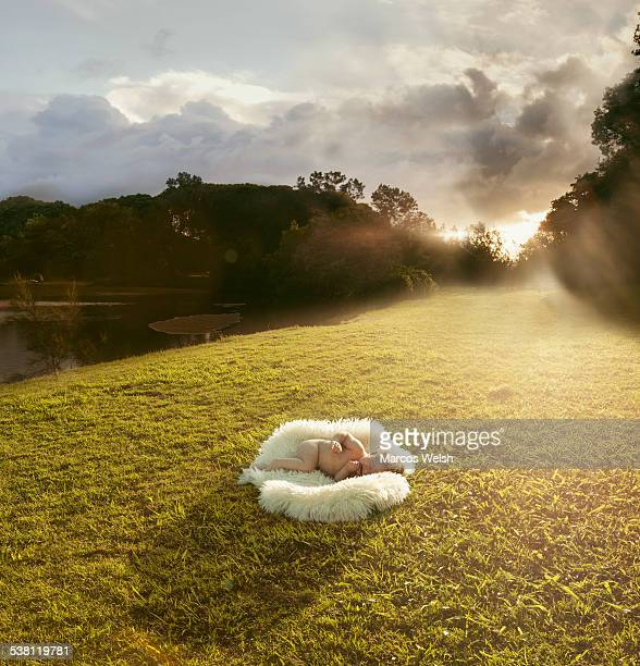 Baby crying lying on sheep skin in nature