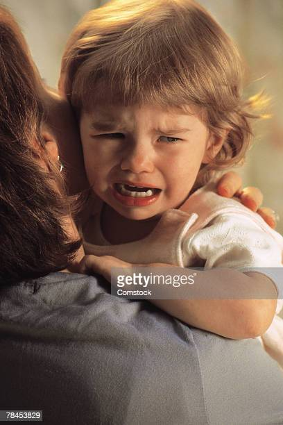Baby crying on mother's shoulder