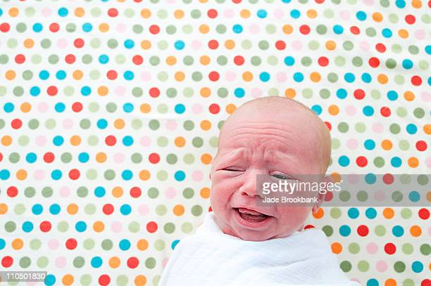 Baby crying on polka dot background