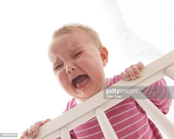 baby crying over bars - baby stock pictures, royalty-free photos & images