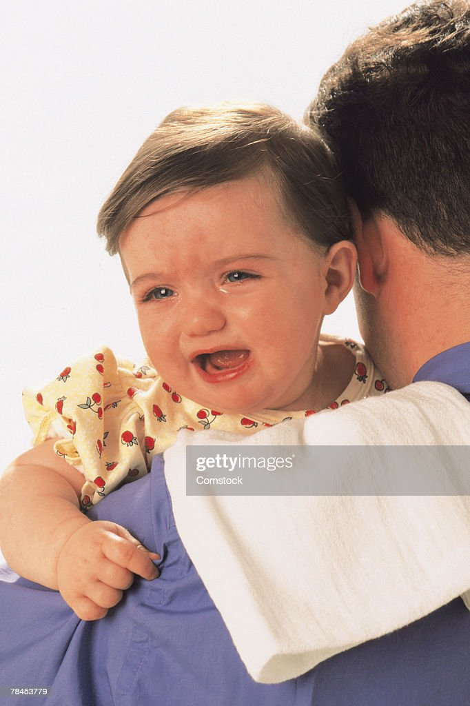 Baby crying over father's shoulder : Stockfoto