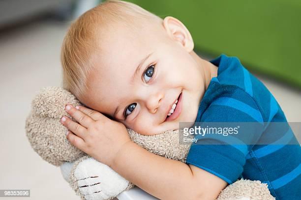 baby cuddling teddy bear