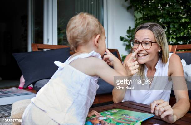 baby daughter and mother looking at a book on the patio - baby pointing stock photos and pictures