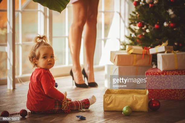Baby decorating Christmas tree with mom