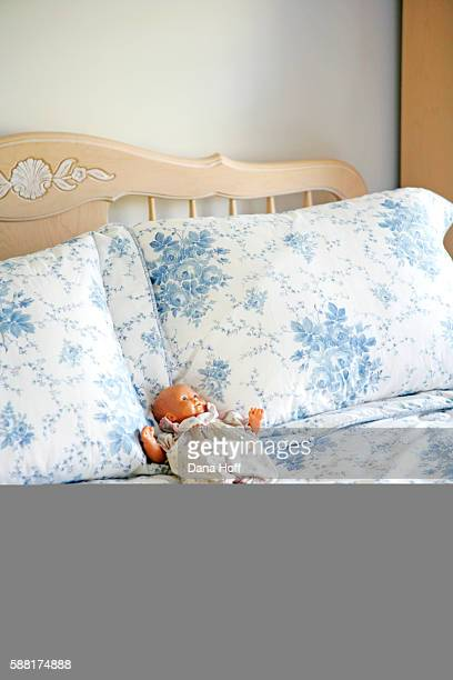 baby doll on blue and white floral bed - dana white stock pictures, royalty-free photos & images