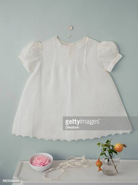 Baby dress over flowers on counter