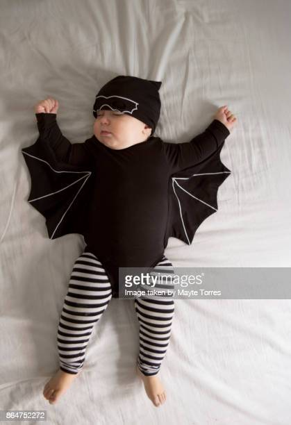 Baby dressed as a bat nappint laying on back
