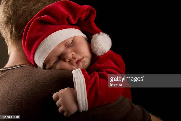 A baby dressed in Christmas clothes while sleeping on father