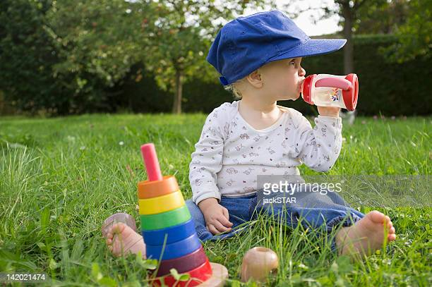 Baby drinking juice in grass