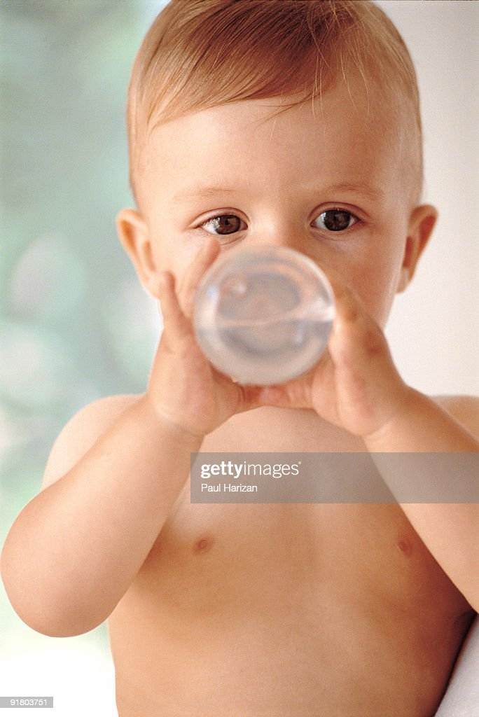 Baby drinking water from bottle : Stock Photo