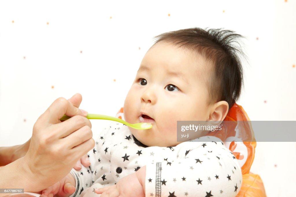 離乳食を食べている日本人の男の赤ちゃん : ストックフォト