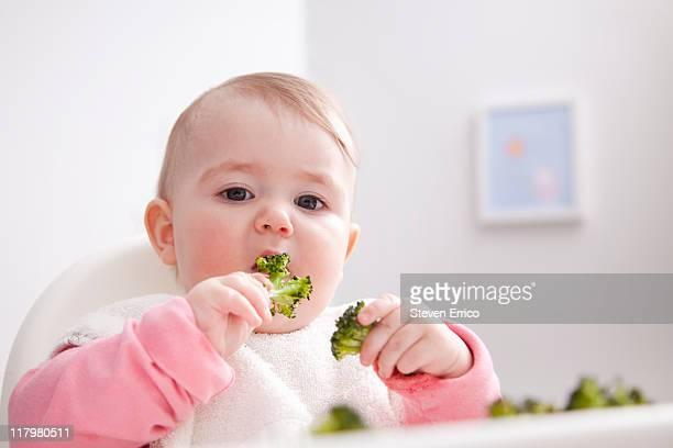 Baby eating broccoli