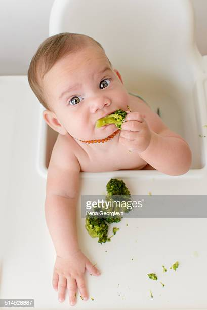 Baby eating broccoli sitting in a high chair