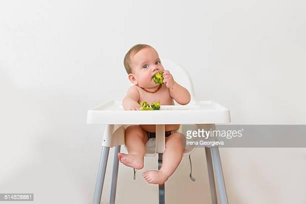 Baby eating broccoli sitting on a high chair