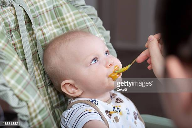 Baby eating solid food spitting some out