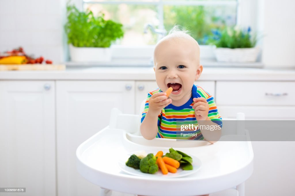 Baby eating vegetables in kitchen. Healthy food. : Stock Photo
