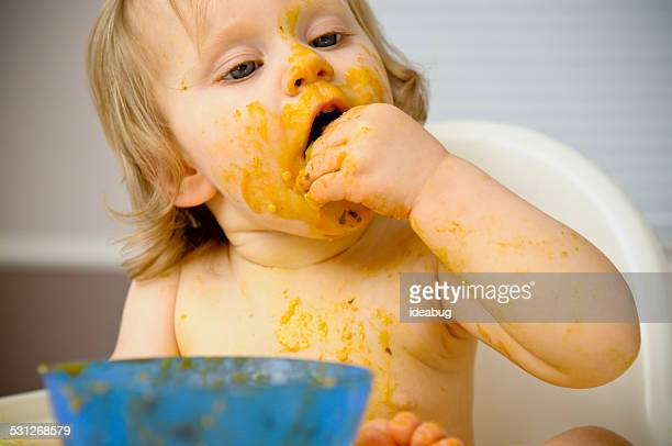 Baby Eating While Covered with Food in High Chair