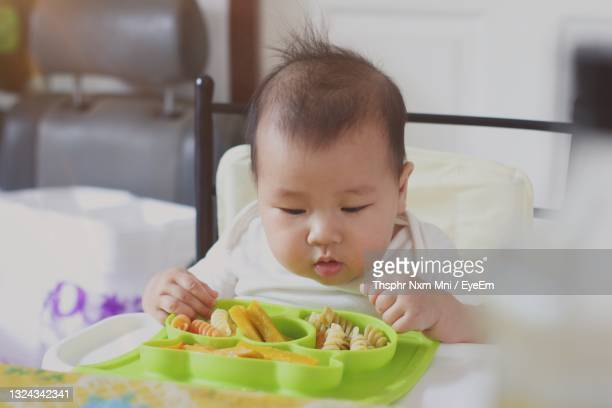 baby eatting for lunch - unknown gender stock pictures, royalty-free photos & images