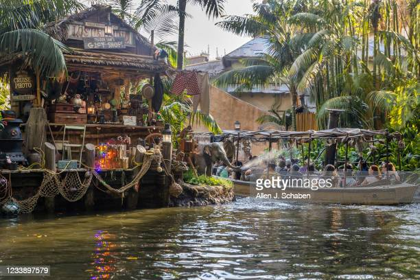 Baby elephant sprays water at a boat as they pass by Trader Sams Gift Shop in Adventureland inside Disneyland in Anaheim, CA, on Friday, July 9,...