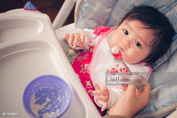 Baby Eurasian girl sitting in high chair while being fed