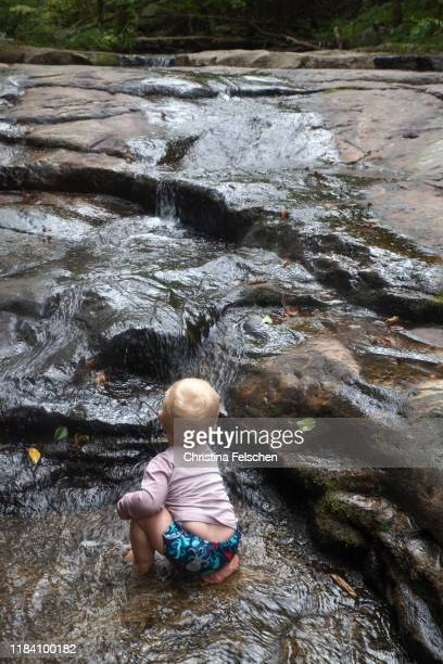 baby exploring a forest creek and waterfall - christina felschen stock pictures, royalty-free photos & images