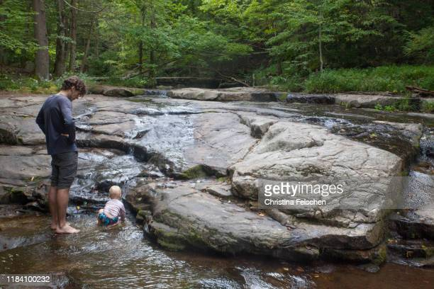 baby exploring a forest creek and waterfall while his father guards him - christina felschen stock pictures, royalty-free photos & images