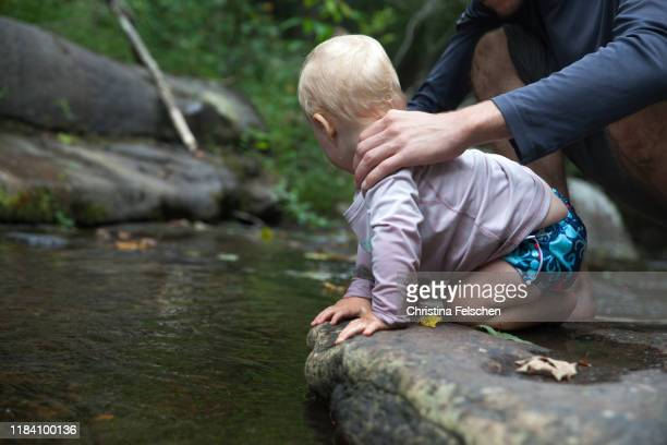 baby exploring a forest creek while his father guards him - christina felschen stock pictures, royalty-free photos & images